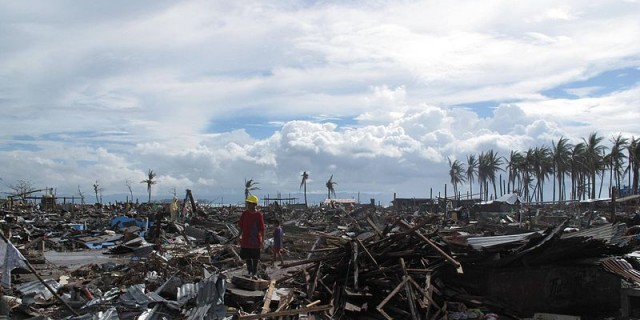 A_man_stands_surrounded_by_the_devastation_wrought_by_Typhoon_Haiyan_in_the_city_of_Tacloban_(11290380063)