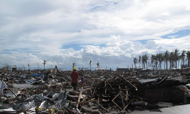 A man stands surrounded by the devastation wrought_byTyphoon Haiyan in the city of Tacloban. Image credit: CC by Wikipedia Commons