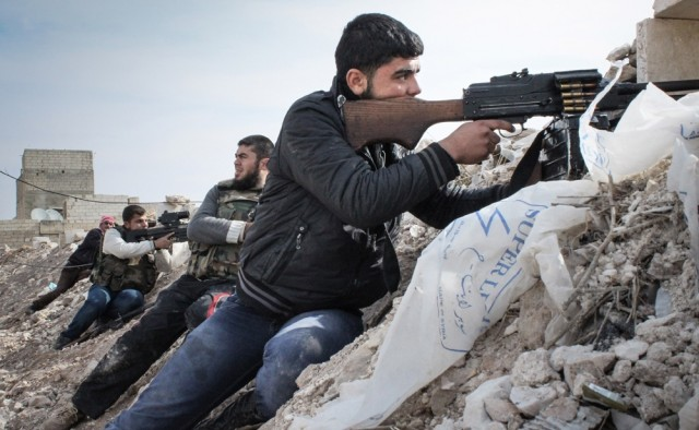 Free Syrian Army rebels fighting against Assad militias on the outskirts of the northwestern city of Maraat al-Numan